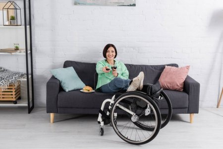 Photo pour Femme souriante avec verre de vin regarder la télévision près de hamburger et fauteuil roulant dans le salon - image libre de droit