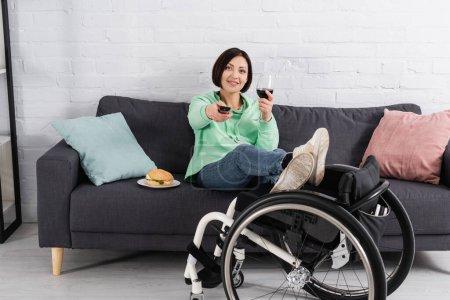 Photo pour Femme handicapée avec télécommande et verre de vin assis près du hamburger et fauteuil roulant à la maison - image libre de droit