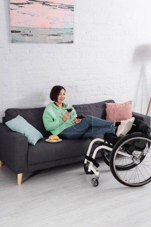 Photo pour Heureuse femme handicapée avec verre de vin regarder film près de hamburger sur canapé et fauteuil roulant - image libre de droit