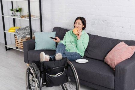 Photo pour Femme mécontente tenant télécommande et manger un hamburger près d'un fauteuil roulant - image libre de droit