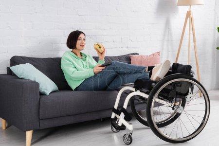 Photo pour Femme souriante tenant un hamburger tout en regardant un film près d'un fauteuil roulant - image libre de droit