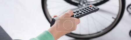 Cropped view of woman clicking channels near wheelchair on blurred background, banner
