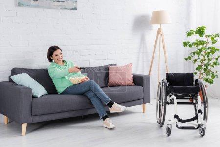 Photo pour Femme gaie avec télécommande et pop-corn regarder la télévision près de fauteuil roulant - image libre de droit