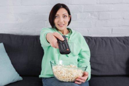 Fernbedienung in der Hand einer lächelnden Frau mit Popcorn auf der Couch vor verschwommenem Hintergrund