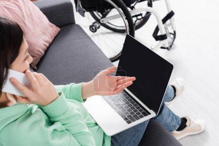 Photo pour Freelancer flou au premier plan parlant sur smartphone et pointant vers un ordinateur portable avec écran vide près d'un fauteuil roulant - image libre de droit