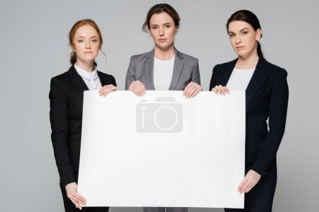 Businesswomen holding blank placard and looking at camera isolated on grey