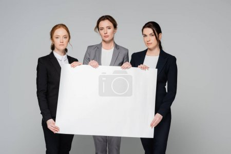 Businesswomen with white placard looking at camera isolated on grey