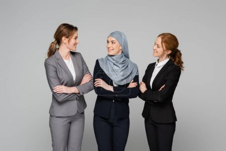 Cheerful businesswomen looking at muslim colleague isolated on grey