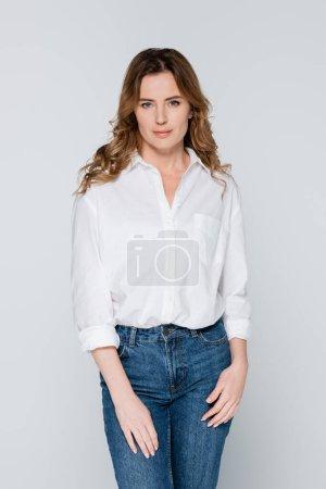 Photo pour Femme adulte en jeans et chemise regardant la caméra isolée sur gris - image libre de droit