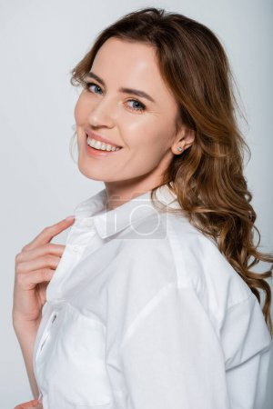 Photo for Adult woman in white shirt smiling at camera isolated on grey - Royalty Free Image