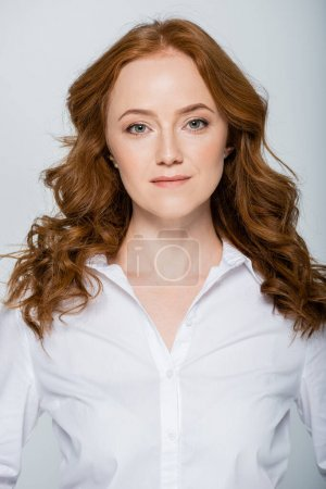 Portrait of redhead woman in white shirt isolated on grey
