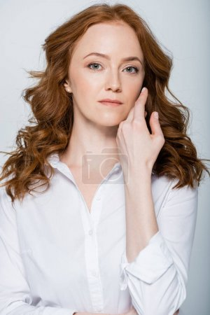 Red haired woman with hand near face looking at camera isolated on grey