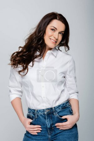 Happy brunette woman in jeans and shirt isolated on grey