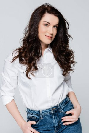 Photo for Brunette woman in jeans and shirt posing isolated on grey - Royalty Free Image