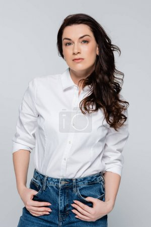 Pretty woman in shirt looking at camera isolated on grey