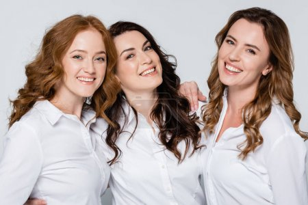 Photo for Adult women in white shirts smiling at camera isolated on grey - Royalty Free Image