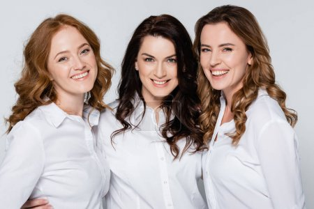 Happy adult women in white shirts posing isolated on grey