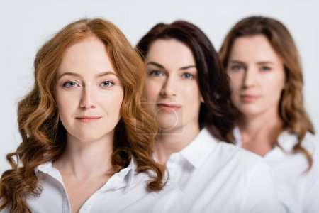 Red haired woman looking at camera near friends on blurred background isolated on grey
