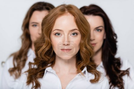 Red haired woman looking at camera near friends blurred on background isolated on grey