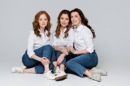 Photo pour Femmes adultes en chemises et jeans assis sur fond gris - image libre de droit
