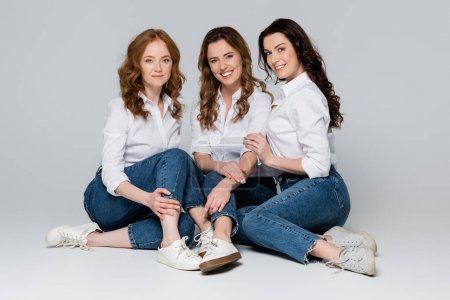 Photo for Smiling friends in jeans looking at camera on grey background - Royalty Free Image