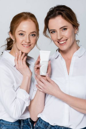 Cheerful women holding tube with cream isolated on grey