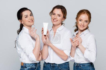 Photo pour Femmes gaies en chemises blanches appliquant crème pour les mains isolée sur gris - image libre de droit