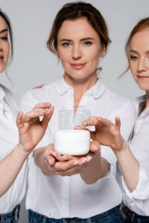 Photo for Jar with cosmetic cream in hand of woman near friends on blurred background isolated on grey - Royalty Free Image