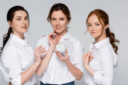 Photo pour Femmes adultes portant des chemises portant une crème cosmétique isolée sur fond gris - image libre de droit