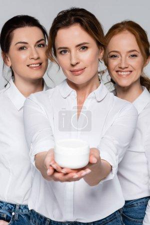 Mujeres sonrientes mirando a la cámara cerca de un amigo con tarro de crema cosmética en primer plano borroso aislado en gris