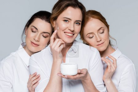Smiling woman applying face cream near friends with closed eyes isolated on grey