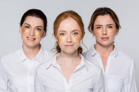 Mujeres adultas con parches en los ojos sonriendo a la cámara aislada en gris