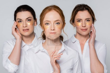 Women in white shirts and eye patches looking at camera isolated on grey
