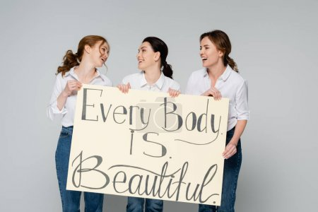 Photo pour Des femmes souriantes se regardant tout en tenant une pancarte avec chaque corps est beau lettrage isolé sur gris - image libre de droit