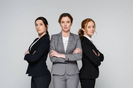 Businesswomen with crossed arms looking at camera isolated on grey