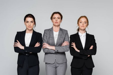 Photo for Adult businesswomen with crossed arms standing isolated on grey - Royalty Free Image