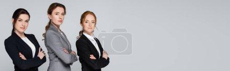 Hübsche erwachsene Geschäftsfrauen blicken vereinzelt in die Kamera auf grauem Banner