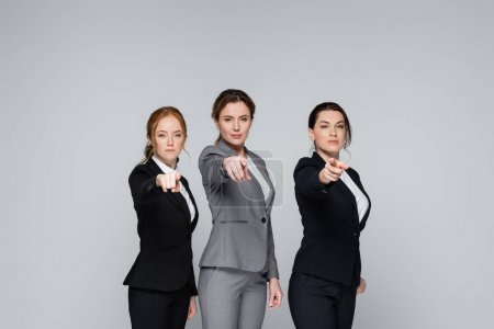 Businesswomen pointing with fingers at camera isolated on grey