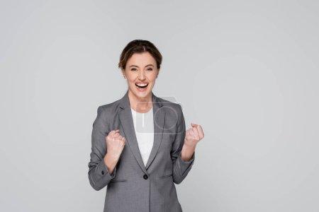 Exitosa mujer de negocios mostrando sí gesto aislado en gris