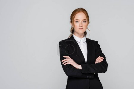 Red haired businesswoman standing with crossed arms isolated on grey