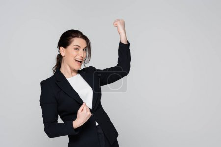 Photo for Cheerful businesswoman showing yes gesture isolated on grey - Royalty Free Image