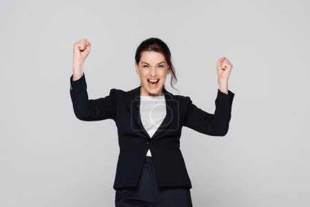 Excited manager showing yes gesture isolated on grey