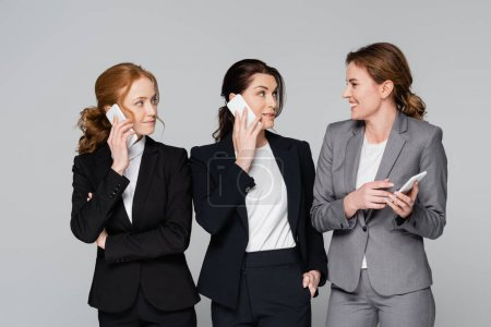 Smiling businesswoman looking at colleagues talking on smartphones isolated on grey