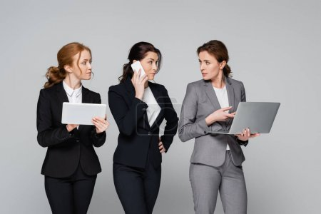 Businesswomen in formal wear using gadgets isolated on grey