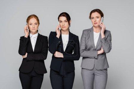 Confident businesswomen talking on smartphones isolated on grey