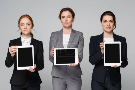 Photo for Businesswomen holding digital tablets with blank screen isolated on grey - Royalty Free Image