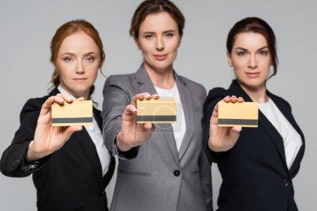 Photo pour Cartes de crédit dans les mains de femmes d'affaires sur fond flou isolé sur gris - image libre de droit