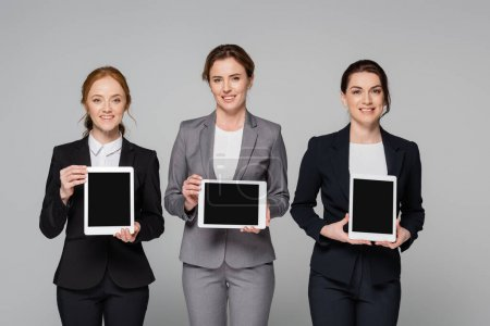 Smiling managers holding digital tablets isolated on grey