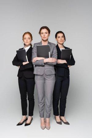 Selbstbewusste Geschäftsfrauen mit Papiermappen auf grauem Hintergrund