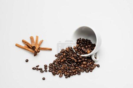 cinnamon sticks near cup with fresh coffee beans on white